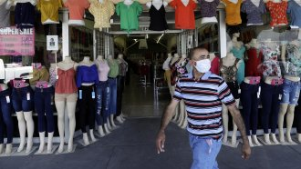 Man in mask passes storefront
