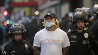 A demonstrator is taken into custody after the city's curfew went into effect in Los Angeles.