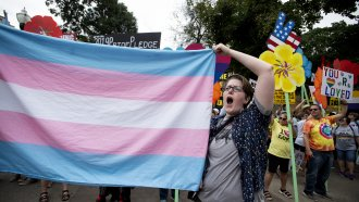 A supporter for the transgender community holds a trans flag.