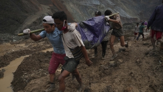 Rescue workers in Myanmar carry a body