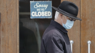 A man walks past a closed business in Shaker Heights, Ohio