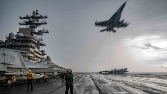 An F/A-18E Super Hornet flies over the flight deck of the Navy's only forward-deployed aircraft carrier USS Ronald Reagan
