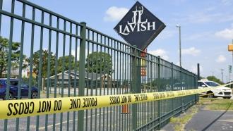 Police tape strung around Lavish Lounge's parking lot