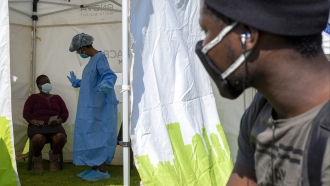A man looks into a tent as a health worker in protective gear collects a sample for COVID-19 testing in South Africa