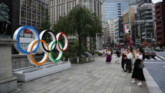 People take pictures of the Olympic rings in Tokyo