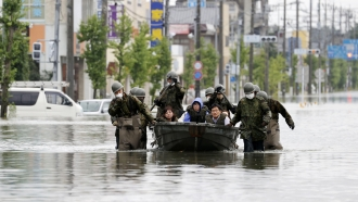 Japanese troops rescue residents from flooding Tuesday in southern Japan city of Omuta.