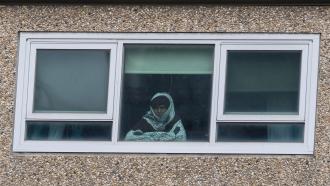 Woman looks through housing complex window