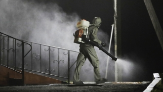 A serviceman of Belarus Ministry of Defence wearing protective gear disinfects a local hospital in the town of Zaslavl