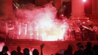 Protesters clash with riot police on the steps of the Serbian parliament during a protest in Belgrade, Serbia, July 11
