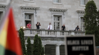 People stand on balcony of mansion of Mark and Patricia McCloskey on July 3 as protests occur below.