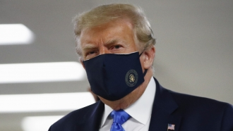 President Donald Trump wears a face mask as he walks down a hallway during a visit to Walter Reed Military Hospital