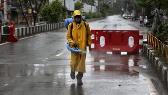 A civic worker sanitizes a deserted road ahead of the lockdown imposed in India.