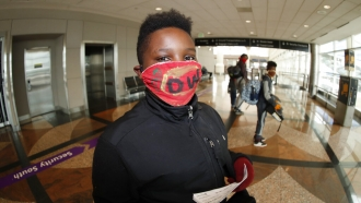 A young traveller wears a face mask