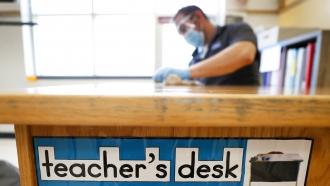 Custodian Joel Cruz cleans a teacher's desk.