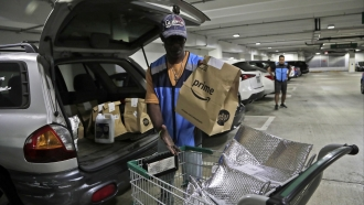 Delivery worker for Amazon Prime loads car with groceries