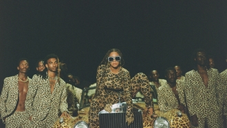 Beyoncé sits on top of leopard-print car surrounded by people