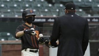 San Francisco Giants ball kid Austin Ginn, left, brings balls to umpire.