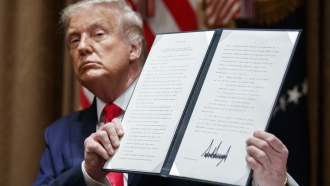 President Trump holds up signed executive order
