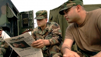 Two soldiers look in on a Stars and Stripes publication