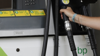 A customer holds of a British Petroleum, BP, petrol pump in west London, Tuesday, Aug. 4, 2020.