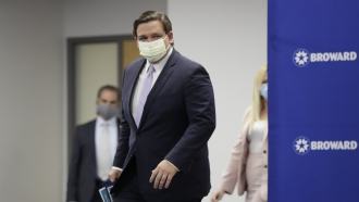 Florida Gov. Ron DeSantis arrives at a news conference.