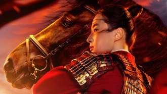 """Mulan"" in full armor stands in front of horse."
