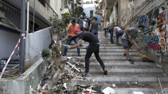 People cleaning up damage in Beirut