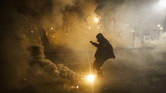 Demonstrator kicks tear gas canister