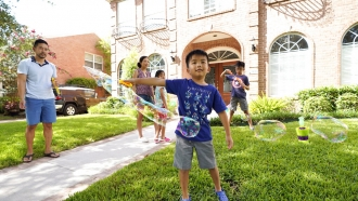 Caption Jesse Yip, 5, makes a bubble as he plays with family at their home.
