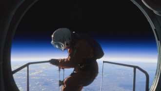 An astronaut climbs out of ship overlooking a planet.