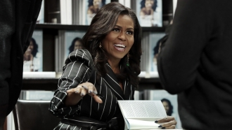 "Former first lady Michelle Obama signing books during an appearance for her book, ""Becoming,"" in New York"