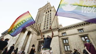 Protester waves two rainbow flags in the middle of Pro-LGBTQ protests