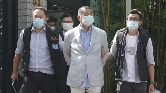 Hong Kong media tycoon Jimmy Lai, center, who founded local newspaper Apple Daily, is arrested by police officers