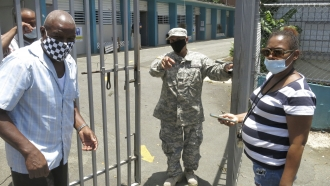 An official turns away two voters at a voting center lacking ballots in Carolina, Puerto Rico, Sunday, Aug. 9, 2020.