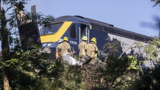 Emergency services attend the scene of a derailed train in Stonehaven, Scotland, Wednesday Aug. 12, 2020.