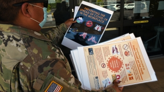 An Arizona National Guard member delivers COVID-19 related posters on Aug. 10, 2020