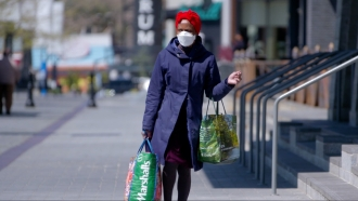 Woman wears a mask and carries shopping bags.