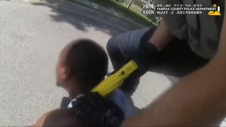 A police officer holds a stun gun to the back of a man's neck