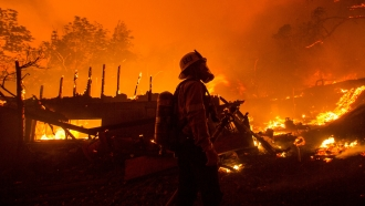 A firefighter watches the Lake Hughes fire consumes a home in Angeles National Forest.