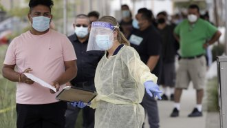 People line up behind a health care worker at a mobile Coronavirus testing site in Los Angeles, California.