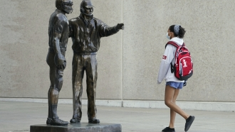 Mask-wearing student walks past statue of legendary University of Nebraska football coach Tom Osborne on Tuesday.
