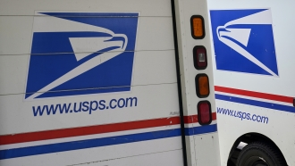 Mail delivery vehicles are parked outside a post office in Boys Town, Neb.