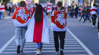 Protesters wear old Belarusian national flags walk during an opposition rally to protest the presidential election results