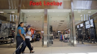 Shoppers walk past a Foot Locker store in Hialeah, Fla.