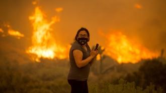 A woman watches as the Bobcat Fire burns in Juniper Hill, Calif.