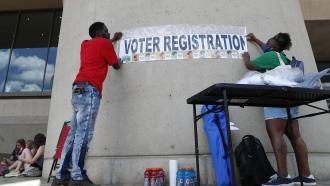 """People hang """"Voter Registration"""" sign"""