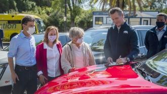 California Gov. Gavin Newsom signs an executive order on the hood of an electric car.