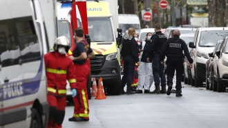 French police officers and rescue workers gather a knife attack near the former offices of satirical newspaper Charlie Hebdo.