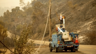 As the LNU Lightning Complex fires burn nearby, a PG&E worker clears a power line blocking a roadway