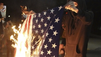 A protester burns an American flag while rallying at the Mark O. Hatfield United States Courthouse on Saturday, Sept. 26